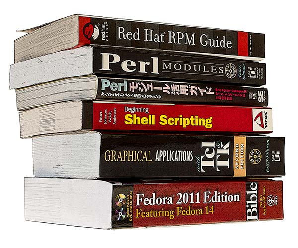 photograph of a stack of Eric's books, including Red Hat RPM Guide, Perl Modules, Japanese version of Perl Modules, Graphical Applications Tcl TK, and Fedora 2011 Edition